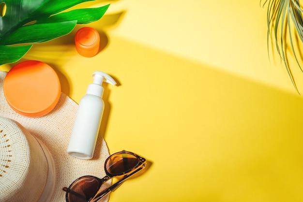 Protetor solar. chapéu de mulher com óculos de sol e creme de proteção spf flat lay em fundo amarelo. acessórios de praia. conceito de férias para viagens de verão