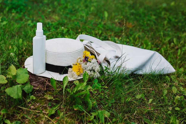 Protetor solar, chapéu de tecido de algodão e saco ecológico deitado na grama verde. férias de verão