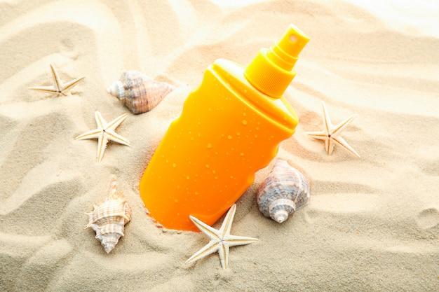 Protetor solar com estrela do mar e conchas do mar na areia clara do mar, closeup e espaço para texto. férias de verão