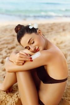 Protetor solar. cuidados com a pele e o corpo. mulher de biquíni, aplicar protetor solar solar no ombro bronzeado.