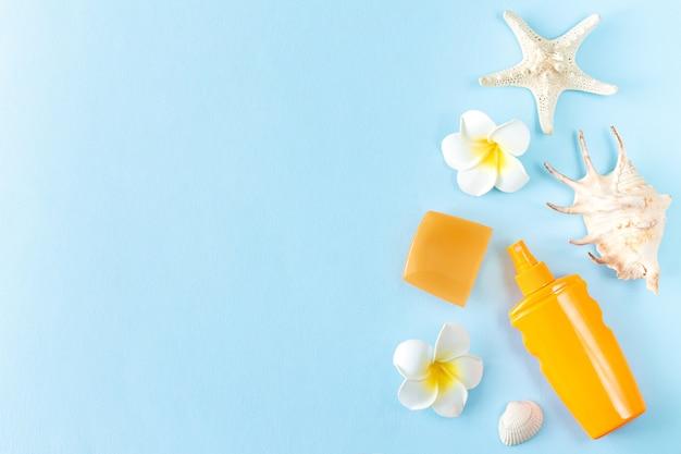 Protetor solar de verão, conchas, estrelas do mar e flores tropicais de frangipani em vista superior do fundo azul