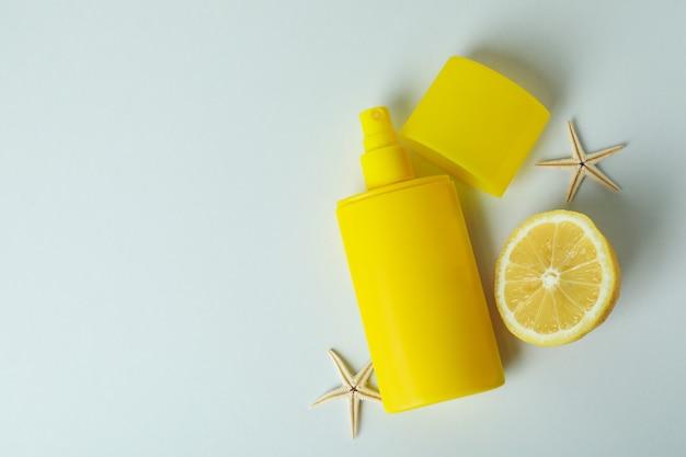 Protetor solar, estrelas do mar e limão em fundo branco isolado