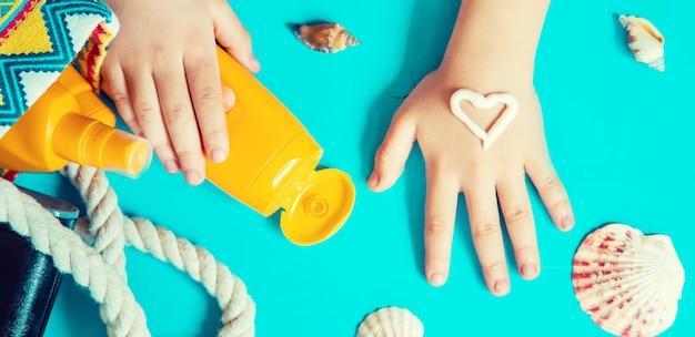 Protetor solar na mão de uma criança.