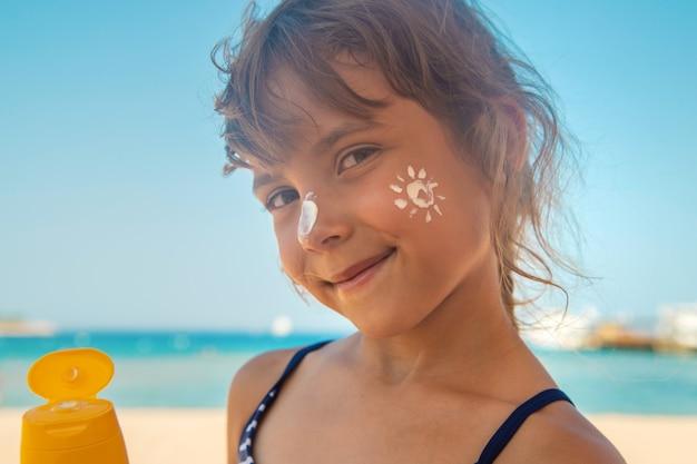 Protetor solar na pele de uma criança. foco seletivo. natureza.