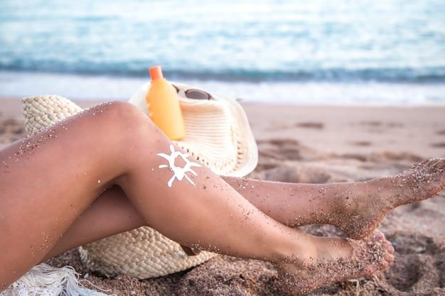 Protetor solar nos pés femininos na praia. parte do corpo. conceito de proteção solar.