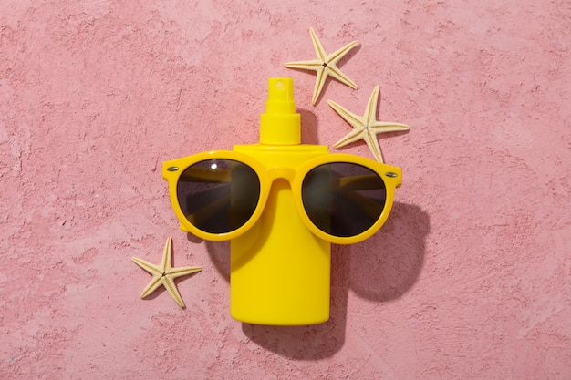 Protetor solar, óculos de sol e estrelas do mar em rosa