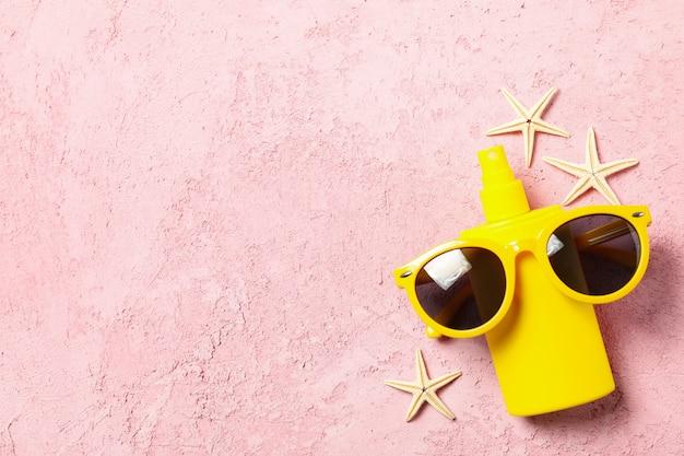 Protetor solar, óculos de sol e estrelas do mar na superfície rosa