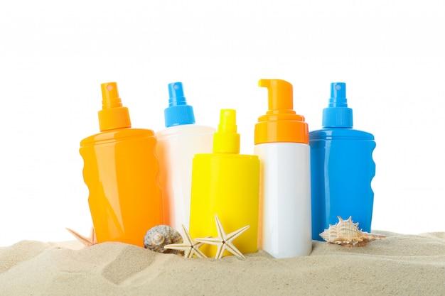 Protetores solares com estrela do mar e conchas do mar na areia clara do mar. férias de verão