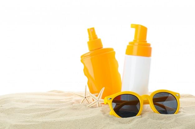 Protetores solares com estrela do mar e óculos de sol na areia clara do mar, isolado no fundo branco. férias de verão