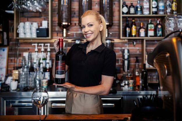 Prova de vinhos e serviço na adega. vista frontal de uma conhecedora de vinhos em um uniforme moderno, trabalhando atrás do bar. mulher segura uma garrafa de bom vinho com ambas as mãos e sorrisos. promoção de vinho