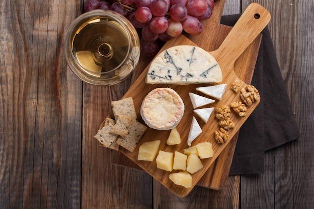 Provando o prato do queijo em um fundo de madeira.