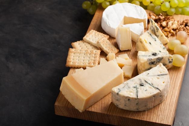 Provando o prato do queijo em uma placa de madeira.