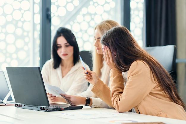 Prováveis jovens trabalhadoras de escritório sentado na sala de reuniões e discutindo seu projeto de negócios conjunto usando dados financeiros e computador.