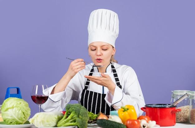 Prove o gosto. pronto para cozinhar um novo prato. salada vegetariana fresca. cozinheiro chefe na cozinha comercial. chef profissional com produtos saudáveis. chef sorridente feliz preparando a refeição com vários vegetais.