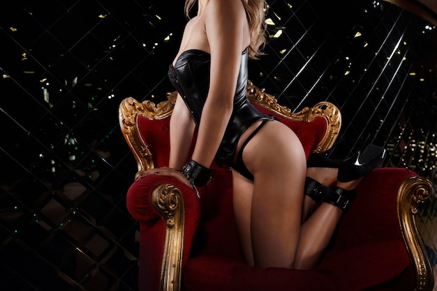 Provocação sensual de uma mulher bdsm sexy em lingerie em uma poltrona