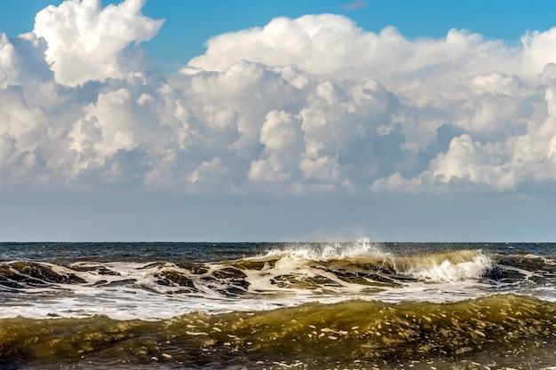 Próximas nuvens de tempestade e ondas quebrando na praia de kijkduin em haia
