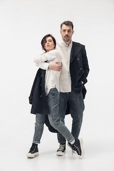 Próximo. casal na moda moderno isolado no fundo branco do estúdio. mulher caucasiana e homem posando com roupas elegantes pretas mínimas básicas. conceito de relações, moda, beleza, amor. copyspace.