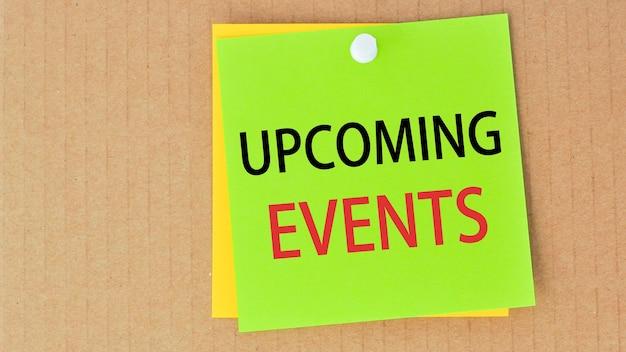Próximos eventos escritos em papel verde e fixados em um quadro de cortiça