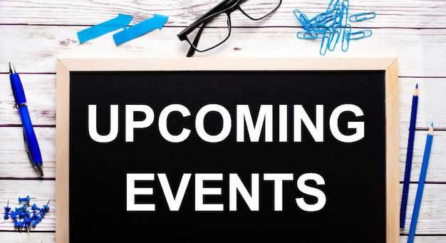 Próximos eventos escritos em um bloco de notas preto ao lado de clipes de papel azuis, lápis e uma caneta
