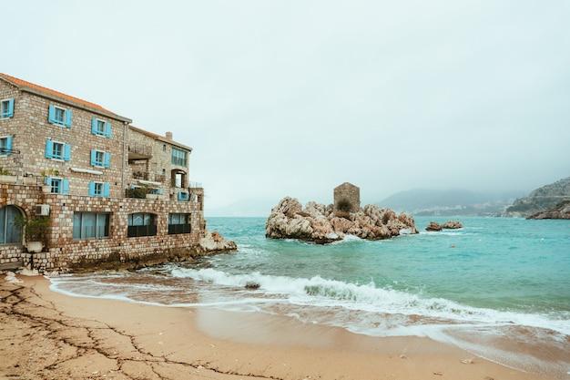 Przno, montenegro. praia, espreguiçadeiras e guarda-sóis na praia, linha de praia.