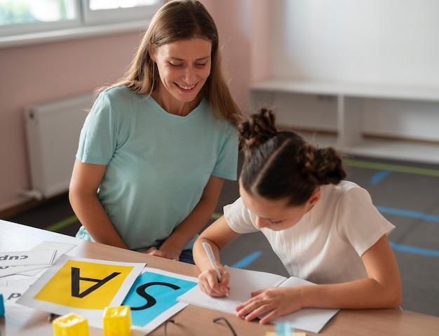 Psicóloga ajudando uma menina na terapia da fala