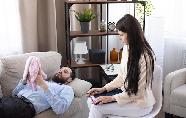 Psicóloga em sessão com seu paciente em seu consultório particular.
