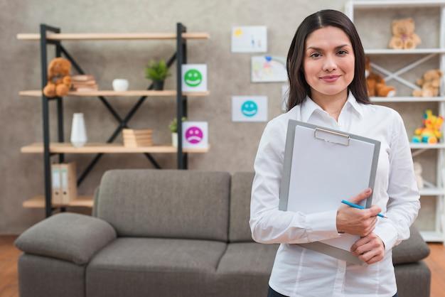 Psicóloga feminina amigável permanente em seu escritório com prancheta e lápis
