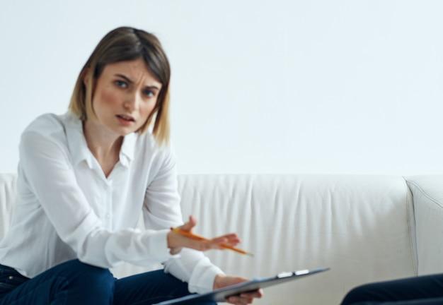 Psicóloga feminina com uma pasta de documentos se senta no sofá em uma sala iluminada.