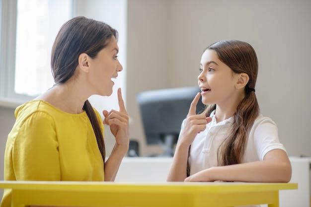 Psicóloga jovem e menina em idade escolar sentadas frente a frente mostrando sinais de dedos