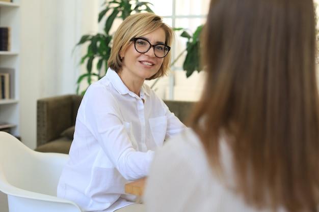 Psicóloga profissional de meia idade conduzindo uma consulta.
