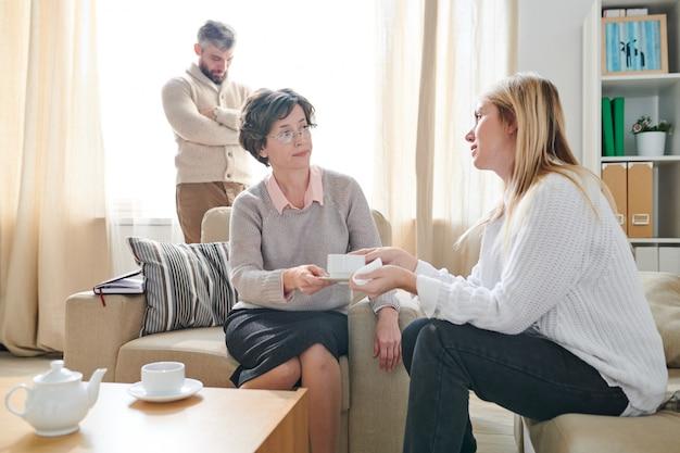 Psicólogo cuidadoso, dando uma xícara de chá ao paciente na terapia ses