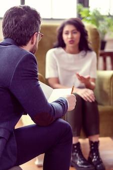 Psicólogo experiente. médico profissional sério ouvindo seu paciente enquanto está no trabalho