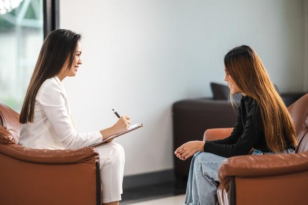 Psicólogo fazendo anotações no histórico médico enquanto entende os problemas de uma paciente