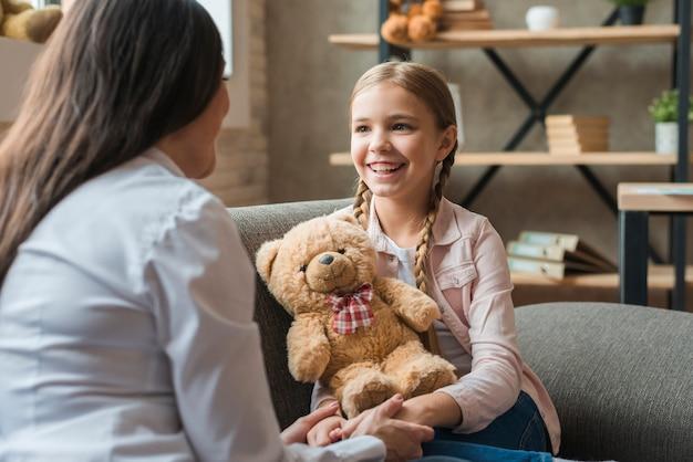 Psicólogo feminino, conversa menina, segurando, urso teddy, durante, terapia, sessão