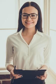 Psicólogo feminino em óculos está segurando uma pasta