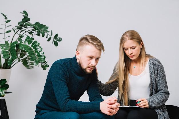 Psicólogo feminino reconfortante paciente masculino deprimido e preocupado