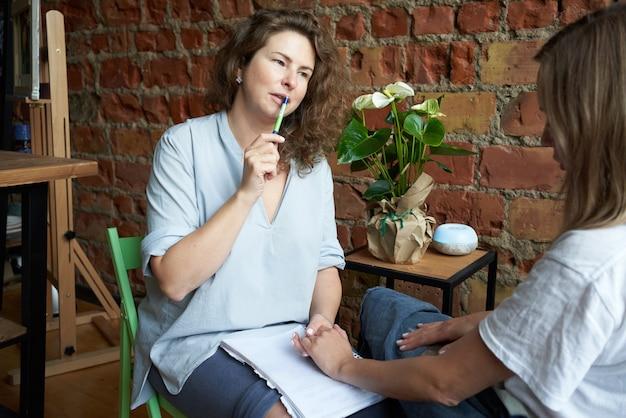 Psicólogo feminino, segurando a mão da mulher, treinador, escrevendo para o caderno.