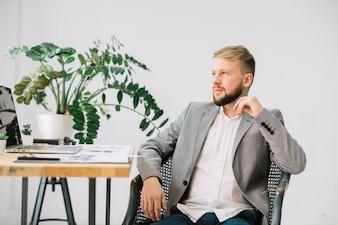 Psicólogo masculino contemplado sentado no local de trabalho em sua clínica