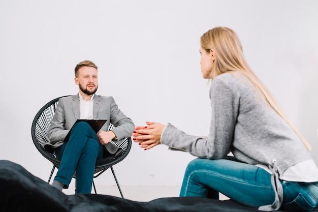 Psicólogo masculino, falando, com, seu, jovem, femininas, paciente, em, terapia, sessão