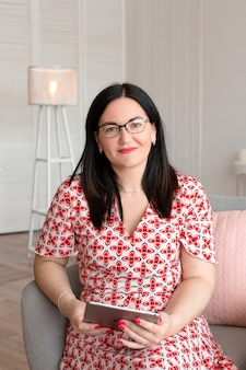 Psicólogo médico profissional com óculos senta-se em um escritório brilhante com um tablet nas mãos e sorrisos