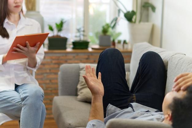 Psicólogo profissional fêmea que conduz uma consulta ao paciente masculino estressante no sofá.