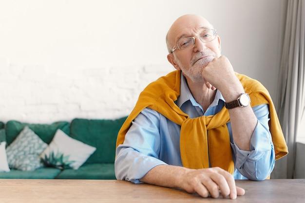 Psicólogo sênior careca com óculos retangulares e suéter amarrado nos ombros, sentado na mesa de madeira vazia do escritório em casa, esperando pelo cliente, com expressão facial atenciosa