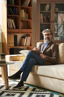 Psicólogo sênior de sucesso em roupas casuais inteligentes e óculos, fazendo anotações de trabalho enquanto está sentado no sofá antes da reunião com o cliente