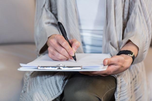 Psicólogo sentado no sofá e tomando notas