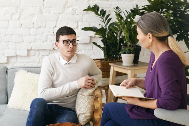 Psicoterapeuta ou conselheira sênior, escrevendo algo no caderno durante a sessão de terapia com jovem homem deprimido e frustrado nos óculos. psicologia, aconselhamento e saúde mental