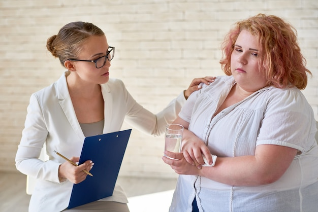 Psiquiatra feminino reconfortante chorando paciente