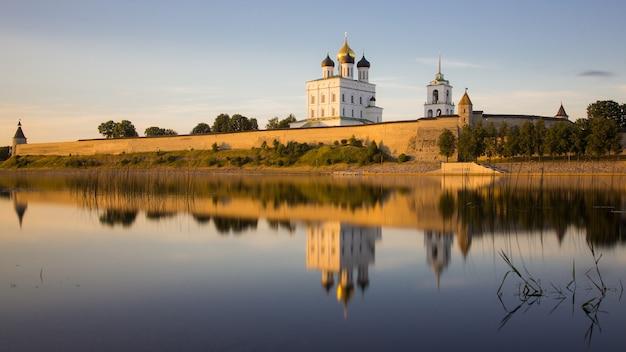 Pskov kremlin com parede de pedra bruta e a catedral ortodoxa russa troitsky