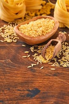 Ptititm ou cuscuz israelense - espécie de macarrão pequeno, tradicional da culinária israelense em um antigo fundo de madeira. copie o fundo do espaço.