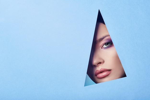 Publicidade belos lábios carnudos brilhantes olhos cor de rosa brilhante, mulher olha no buraco colorido papel azul, salão de beleza. maquiagem olhos, publicidade rosto cuidados, lábios perfeitos, moda beleza maquiagem cosméticos