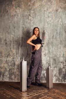 Publicidade de equipamentos industriais para obras de construção de estradas. jovem mulher com uniforme de trabalho anuncia cilindro pneumático de distribuição na sala de produção da fábrica. conceito de desenvolvimento industrial